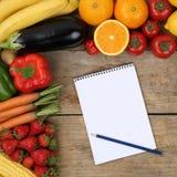 Einkaufsliste mit Obst und Gemüse auf einem hölzernen Brett Stockbild