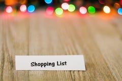 Einkaufslistekonzept auf hölzernem Brett und farbigen Lichtern, selektiver Fokus, Raum für Kopie Lizenzfreie Stockfotografie