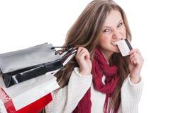 Einkaufsmädchen, das von der Kreditkarte bitting ist Stockfoto