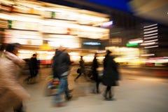 Einkaufsmenge, die auf Bürgersteig an der Dämmerung geht Stockbild