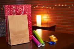 Einkaufspapiertüten auf einer Tabelle mit irgendeiner Geschenkpapierverpackung lizenzfreies stockbild