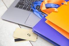 Einkaufstaschen, Kreditkarte, Laptop auf Schreibtisch stockfoto