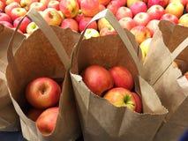 Einkaufstaschen mit frischen organischen Äpfeln für Verkauf Stockfotografie
