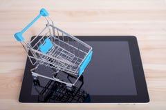 Einkaufswagen über einem Tablet-PC auf Holztisch stockbilder
