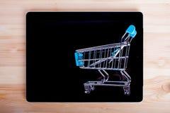 Einkaufswagen über einem Tablet-PC auf Holztisch, Draufsicht stockfotografie