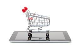 Einkaufswagen über einem Tablette PC Stockbild