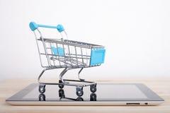 Einkaufswagen ?ber einem Tablet-PC auf Holztisch stockbild
