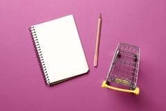 Einkaufswagen, Notizbuch des leeren Papiers mit Stift auf einem rosa Hintergrund lizenzfreie stockfotos