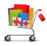 Einkaufswagen voll der Einkaufenbeutel und der Geschenkkästen Stockfotos