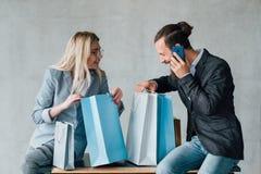 Einkaufszufällige Freizeitpaare des genusses sitzen Taschen lizenzfreies stockbild