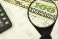 Einkommensberechnungskonzept Vergrößerungsglas erhöht Bezeichnung von hundert Dollar auf Zahlhintergrund stockfotografie