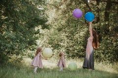 Einkreisen der Mutter und zwei Tochterhändchenhaltens Familienzeit zusammen Lustige Zeit Mädchen mit Ballonen Weicher Fokus stockbild