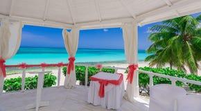 Einladende Ansicht der Betäubung vom Innere des verzierten Heiratsgazebo auf ruhigem Ozean des tropischen Strandes und blauem Him Stockfotos