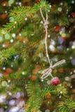 Einladung des neuen Jahres Erdbeeren, die an einem Fichtenzweig hängen Lizenzfreie Stockfotos