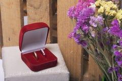 Einladungskarte mit Perlendekoration und Rosen Boutonniere auf weißem Hintergrund Eheringe in einem Kasten, Lüge auf der Gewebeob Lizenzfreie Stockbilder
