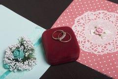 Einladungskarte mit Perlendekoration und Rosen Boutonniere auf weißem Hintergrund Einladungskarten und Eheringe in einem Kasten,  Lizenzfreie Stockfotografie