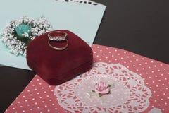 Einladungskarte mit Perlendekoration und Rosen Boutonniere auf weißem Hintergrund Einladungskarten und Eheringe in einem Kasten,  Stockbilder