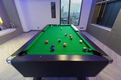 Einlegen Sie grüne Tabelle des Pool-Billard mit ganzem Satz Bällen in einer Mitte eines Spiels in einem modernen Spielraum her Stockfoto