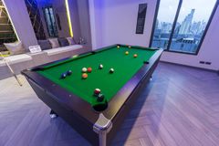 Einlegen Sie grüne Tabelle des Pool-Billard mit ganzem Satz Bällen und zwei poo Stichwörtern in einem modernen Spielraum her Stockbilder