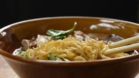 Einoedels met gekookte eend in Chinese kruid bruine soep bij kom het plukken door te eten eetstokjes stock footage