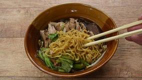 Einoedels met gekookte eend in Chinese kruid bruine soep bij kom het plukken door te eten eetstokjes stock video