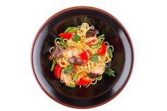 Einoedels met kip en groenten onder teriyakisaus, op witte achtergrond wordt geïsoleerd die Einoedels in een zwarte plaat Royalty-vrije Stock Afbeelding