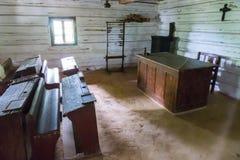 Einrichtungsgegenstände der hölzernen Schreibtische des alte Schulklassenzimmers ländliche Schulversanden Boden und Abakus auf de Stockfotografie