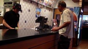 Einrichtungslebensmittel der Leute und Bargeld an KFC-Kasse zahlen stock footage