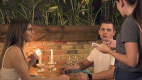 Einrichtungsnahrung des Mannes und der Frau für romantisches Abendessen mit Kerzen, wenn Restaurant geglättet wird Kellnerin, die stock video