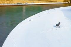 Einsame Bank im Schnee über dem Fluss Stockbild