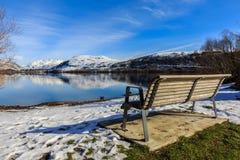 Einsame Bank im Winter mit Seeblick Stockbilder
