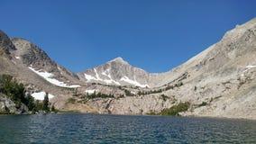 Einsame Bergspitze über einem See Stockfoto