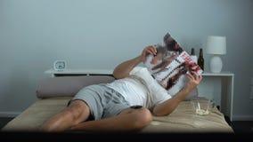 Einsame Blätterbildungszeitschrift des Mannes enthusiastisch mit dem erwachsenen Inhalt, der im Schlafzimmer liegt stock video