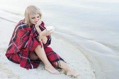 Einsame blonde Frau auf dem Strand mit Schale des heißen Getränks, warmes rotes Plaid Stockbild