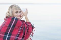 Einsame blonde Frau auf dem Strand mit Schale des heißen Getränks, warmes rotes Plaid Stockfoto