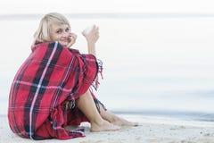Einsame blonde Frau auf dem Strand mit Schale des heißen Getränks, warmes rotes Plaid Stockfotografie