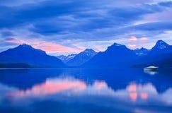 Einsame Boots-und Sonnenaufgang-Farben auf ruhigem Mountainsee Stockbilder