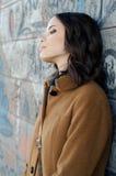 Einsame Dame, die auf der Graffitiwand in der städtischen Umwelt sich lehnt Lizenzfreie Stockfotos