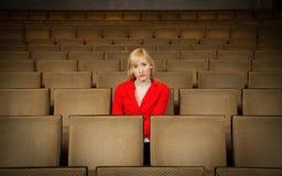 Einsame, deprimierte Frau, die allein im leeren Theater sitzt Stockfotografie