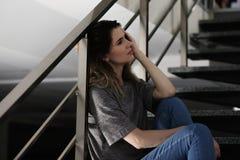 Einsame deprimierte Frau, die auf Treppe sitzt Stockfoto