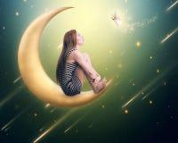 Einsame durchdachte Frau, die auf dem sichelförmigen Mond sitzt Stockbilder