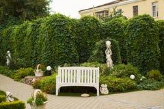 Einsame englische Gartenbankgrünhintergrund-Engelsskulptur lizenzfreie stockfotografie