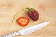Einsame Erdbeere auf einem hackenden Brett Lizenzfreies Stockbild