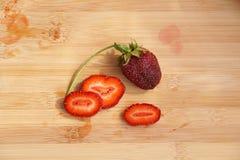 Einsame Erdbeere auf einem hackenden Brett Lizenzfreie Stockfotos