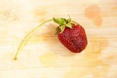 Einsame Erdbeere auf einem hackenden Brett Lizenzfreies Stockfoto