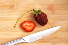 Einsame Erdbeere auf einem hackenden Brett Stockfotos