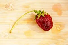 Einsame Erdbeere auf einem hackenden Brett Lizenzfreie Stockfotografie