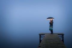 Einsame Frau auf Brücke mit Regenschirm stockfotos
