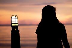 Einsame Frau, die allein zu einer Zeit als Seesonnenuntergang sitzt sind reizende abstrakte Art Stockbilder