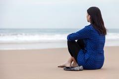 Einsame Frau, die auf dem Sand eines Strandes sitzt Stockfotografie